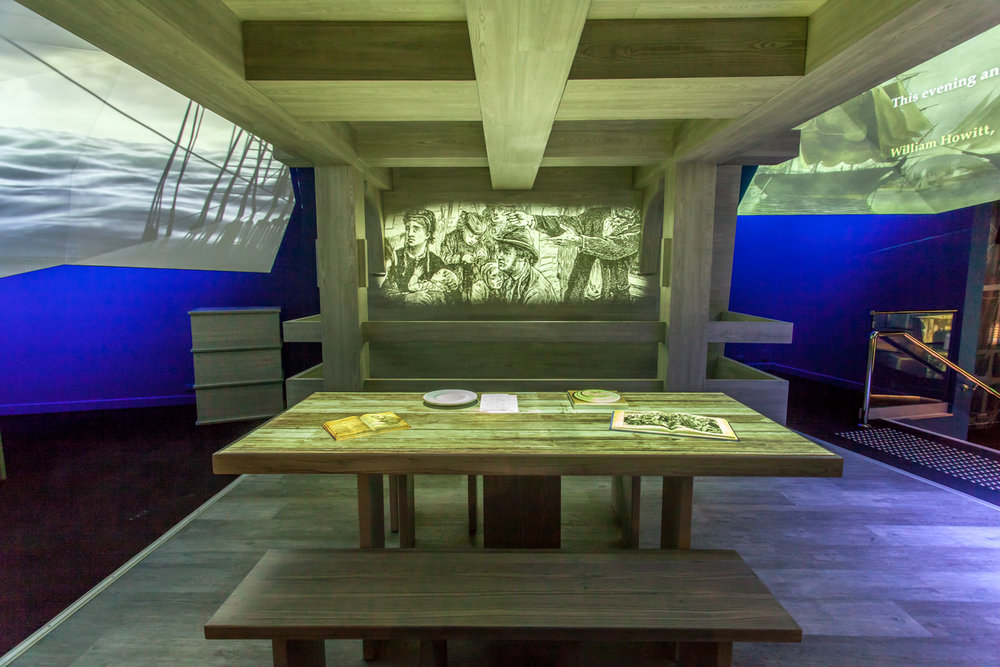 SHIPS TABLE - an interactive projection mapped exhibit with a dual screen video playing on the bulkhead.