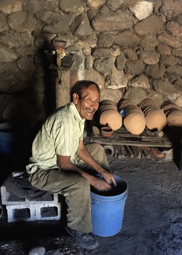 Maximilliano packing salt for sale.  The clay bowls in the background are used to cook the salt in an open fire for 12 hours to get the crystal form.