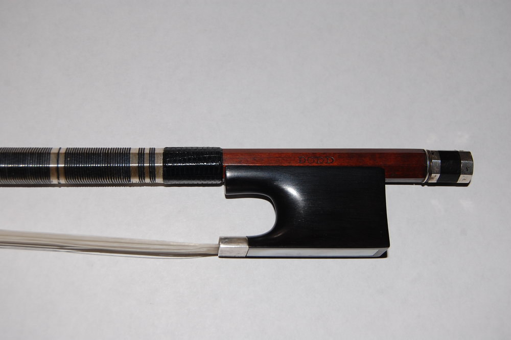 We've recently aquired this very fine 'cello bow by renowned English bowmaker 'John Dodd'. Beautifully made and fully restored, this bow weighs 83g. It is silver mounted with an ebony face and decorative silver and thread lapping. John Dodd was born in 1752, it's very rare to have a bow of this age in such wonderful condition.