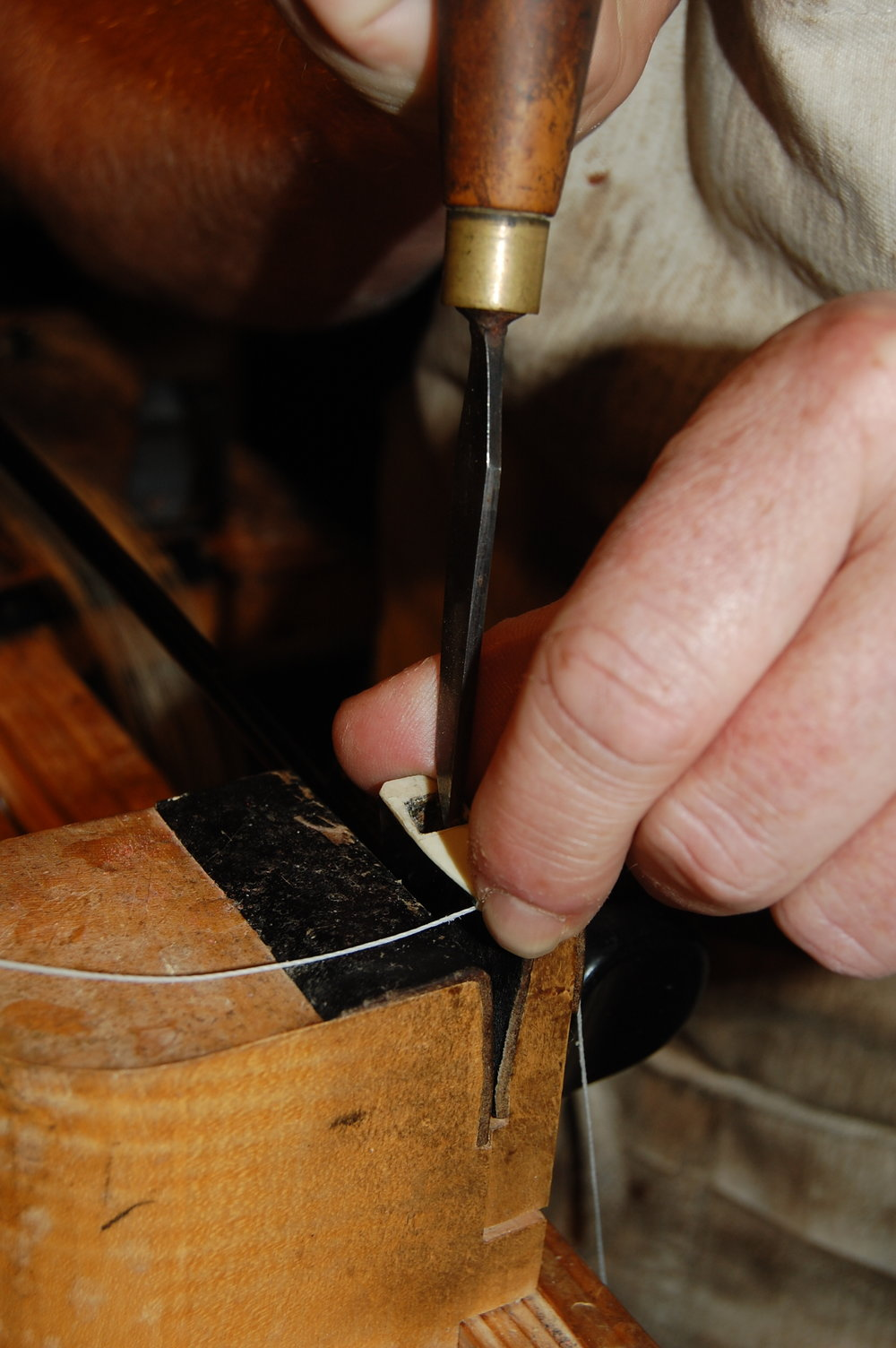 New wedges often need cutting, these hold the hair firmly in place. Three wedges are used on a bow; the frog, the head and the spreader wedge. The top edge of the mortice inside the bow head needs to be absolutely straight in order to acheive even tension throughout the length of the bow.