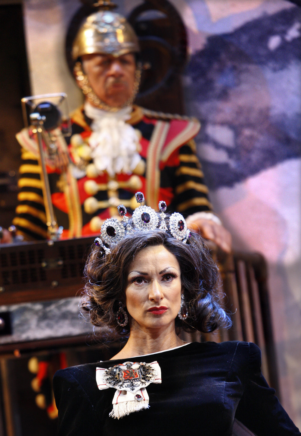 Exit the King foreground Indira Varma as Queen Marguerite background Derek Griffiths as the Guard in , photo by Simon Annand.JPG