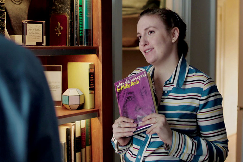 What's New:  Hannah (Lena Dunham) with a copy of Roth's When She Was Good, in Girls