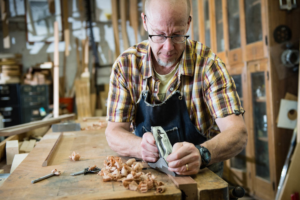 Maura Wayman Photography, Photography, Corporate Photography, stock, stock images, Massachusetts, Boston, Metro West, Wellesley, man, wood woodworker, tools, furniture, furniture maker, checkered shirt, glasses, bald,