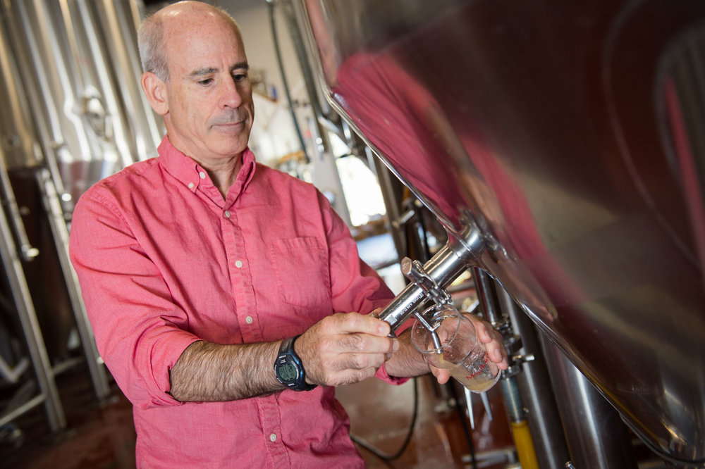 Maura Wayman Photography, Photography, Corporate Photography, stock, stock images, Massachusetts, Boston, Metro West, Wellesley, man, wood, bald, pink shirt, beer, pouring beer, beer in vats, brewery,