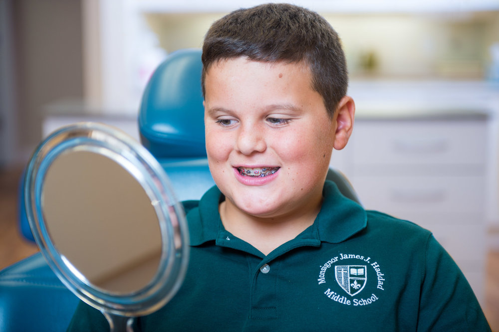 Maura Wayman Photography, Photography, Corporate Photography, stock, stock images, Massachusetts, Boston, Metro West, Dentist, Dentist office, patient, braces, boy, green shirt, mirror, smile,