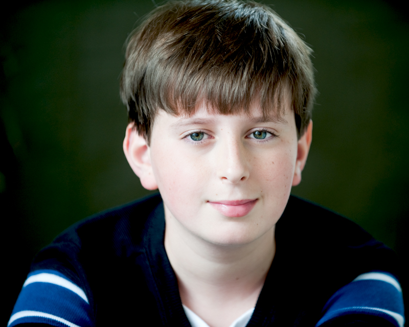 headshot of boy with green eyes and blue shirt