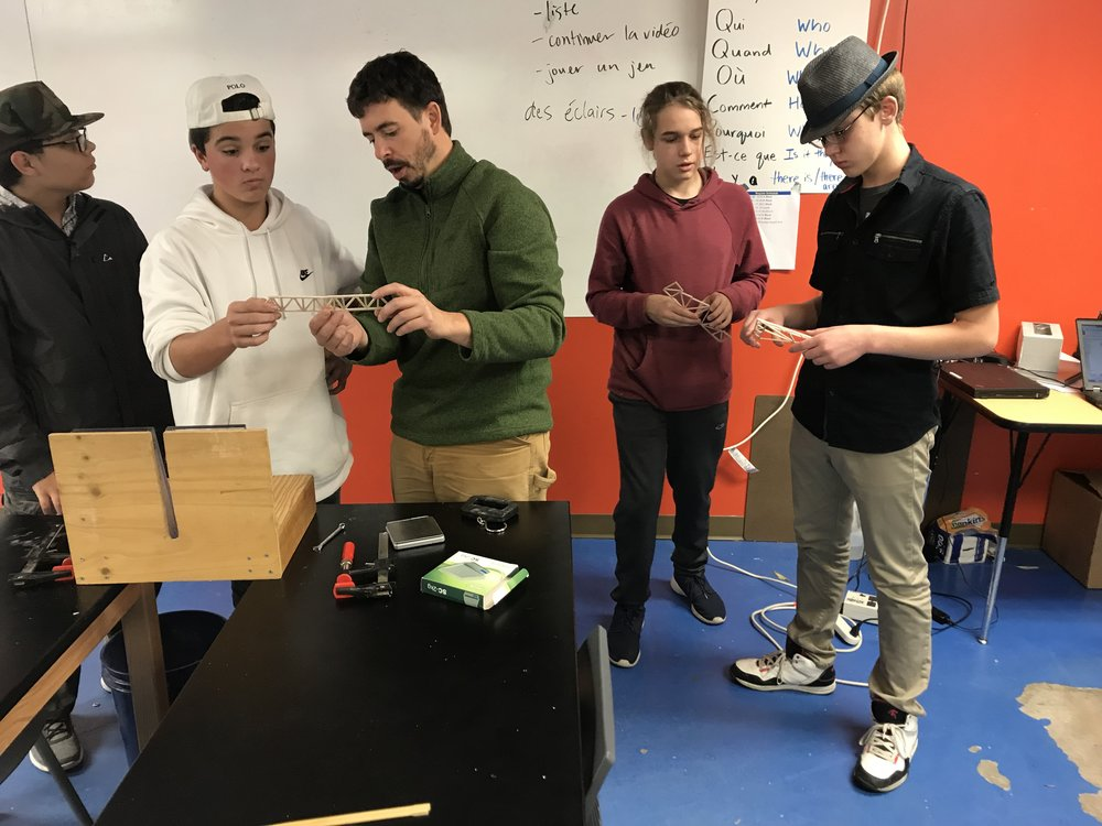 Students in Introduction to Engineering analyze their truss bridges with instructor, Jon Amory.