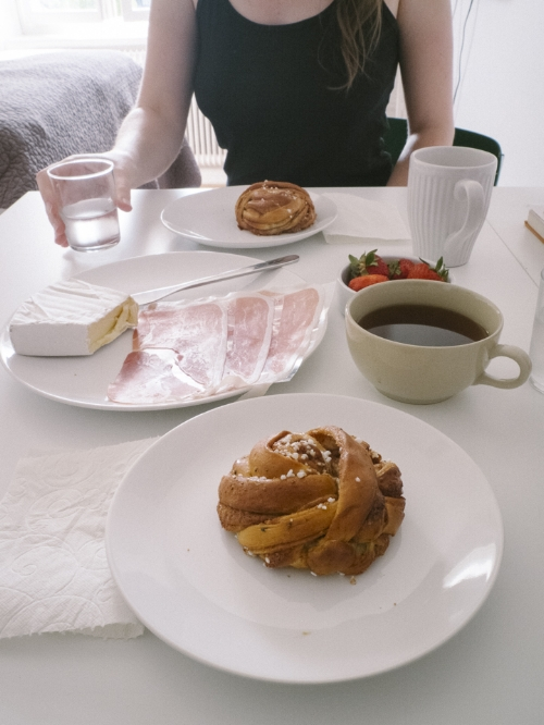 Enjoying a simple breakfast of cheese, cinnamon buns, and local strawberries from a grocery store in Nytorget, Stockholm, 2016.