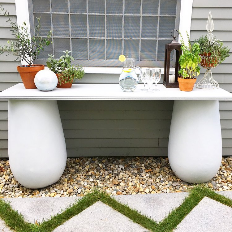 The console table I made... The two pedestals are old giant pots I repainted. And the actual table part is a wooden door I bought at Lowe's, with a pretty wooden trim that I added on for the edge. Voila! The perfect outdoor console table for some planted herbs and to prep food for the grill.
