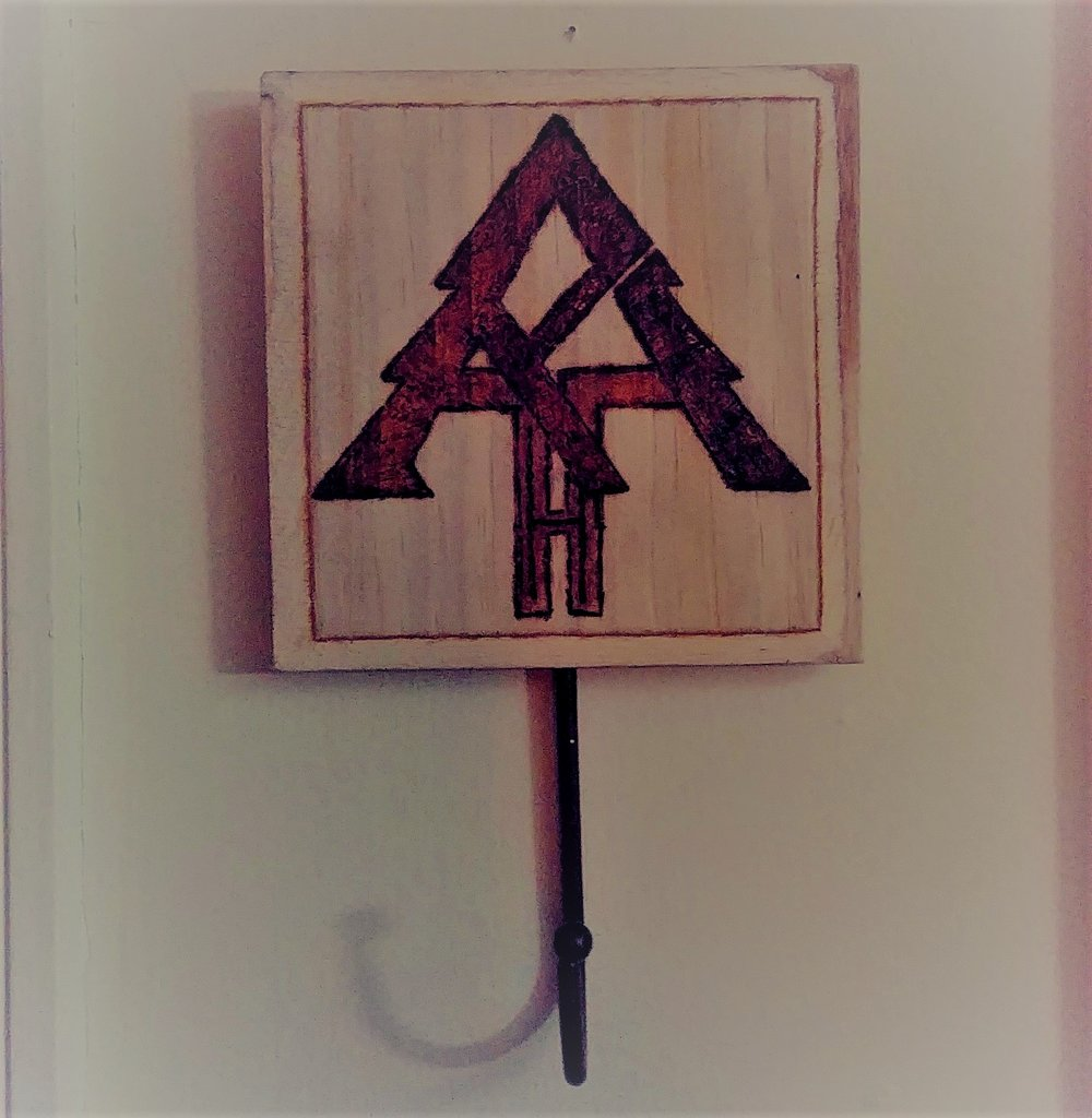 "Alt Hearth Logo - On this key holder is an alternative logo for hearth.earth burned into the wood. The letters: H E A R T H are within this logo that is supposed to be a more tribal alternative to the primary logo that is much more colorful/iconic. It is also supposed to mimic the look of the Appalachian Trail symbol with a bit of a twist. Hint: the ""E"" is sideways, the ""H's"" are within the ""T"", and the ""R"" makes up the left side of the ""A"""