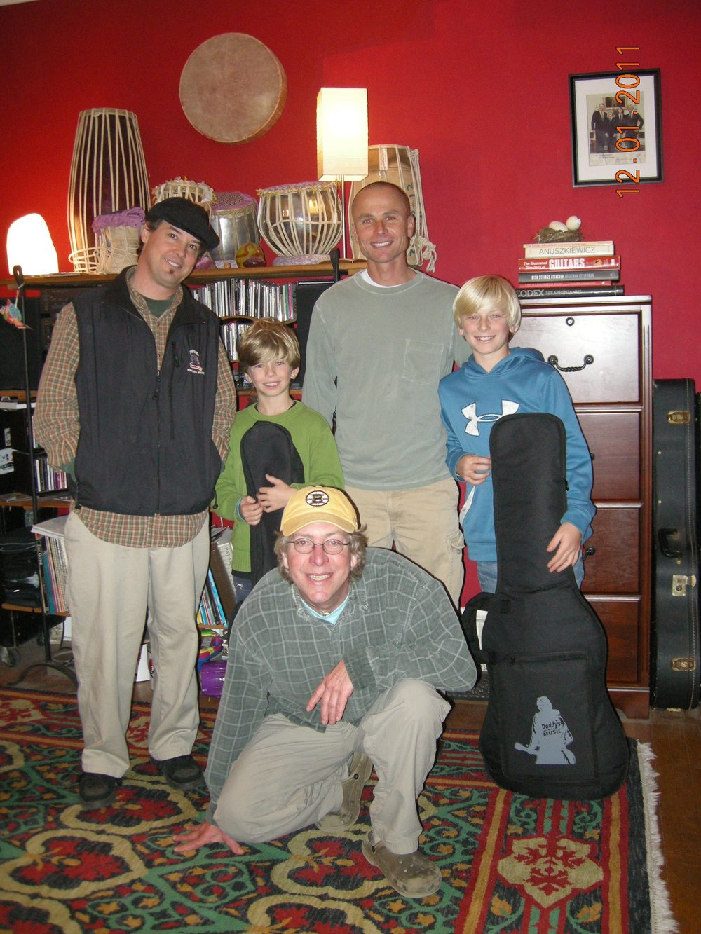 Felix (left) in the music studio with two young students and their dads.