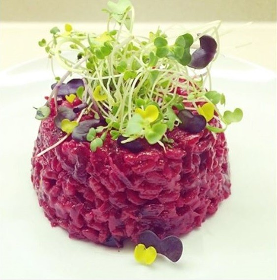 A vegan beet risotto with a daikon sprout garnish