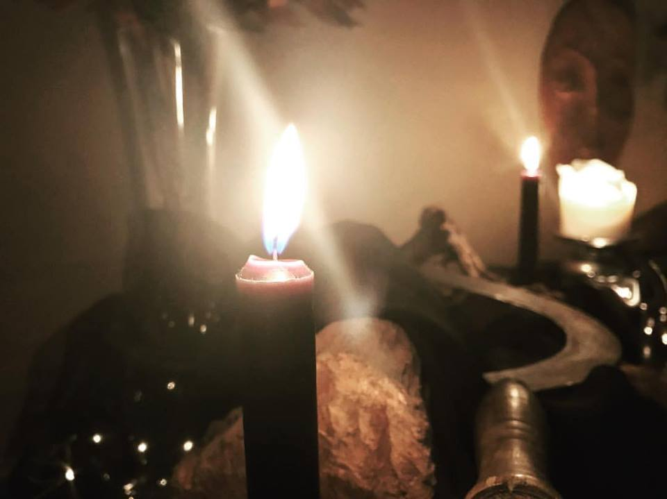 Celebriamo la Dea Crona. La natura muore e le offerte dell'ultimo raccolto bruciano nei fuochi. La notte prende il sopravvento sulla luce del giorno. Inizia l'inverno e ci lasciamo alle spalle l'abbondanza della stagione luminosa, alla ricerca di un covo sicuro all'interno, mentre accogliamo il buio. Nelle nostre anime ci rifugiamo e lí abitiamo, invitando la Dea a svelare le nostre verità. Chiamiamo i Suoi nomi per lasciare andare quello che non ci serve più. Quello che lasceremo nel cuore d'inverno, perchè si trasformi e rinasca a primavera. Lei è l'oscuro Calderone della nostra trasformazione. Lei è Signora della Falce e delle forbici. È la vulva universale della morte e della rinascita. Lei è Cerridwen, Persefone e Atropo. Noi la onoriamo come la madre Morte in tutte le sue forme. Lei che schiude il velo. In questa notte crocevia, sentiamo le voci degli avi nel nostro sangue che scorre scuro nel nostro corpo. Onoriamo i nostri antenati. L'eco delle nostre radici nella nostra anima. Raccogliamo Famiglia e amici e intagliamo i frutti dell'ultimo raccolto dell'anno. Nella notte, una luce per gli spiriti e le creature che ritornano attorno a noi. Onoriamo coloro che sono venuti prima di noi in questa notte dell'animo di saggezza, rivelazioni e trasformazioni. Siamo ombre, corvi. Rivendichiamo il nome di streghe, uomini e donne, creature di spirito. Onoriamo la stagione delle tenebre. Onoriamo la Dea Crona.