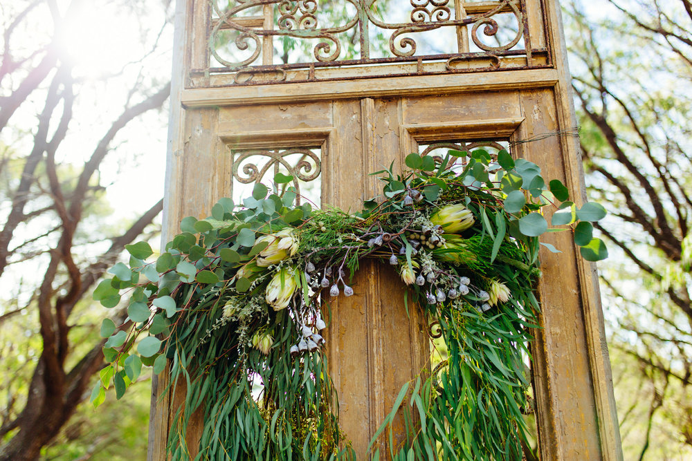 Solitaire ceremony door and florals