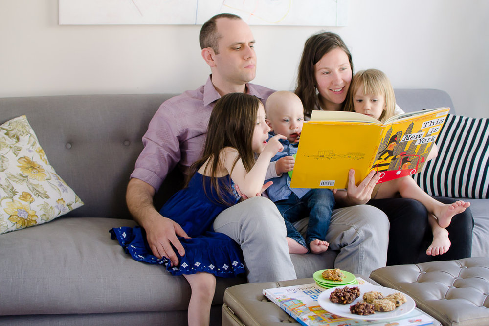 Family of five cuddling on the couch reading a children's book