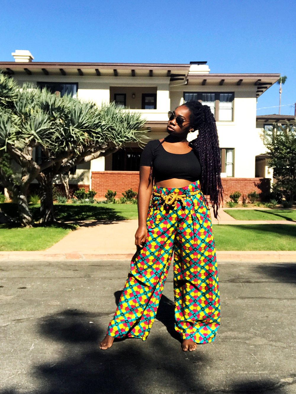 Femi wearing African print wide leg pants and black crop top standing in the street
