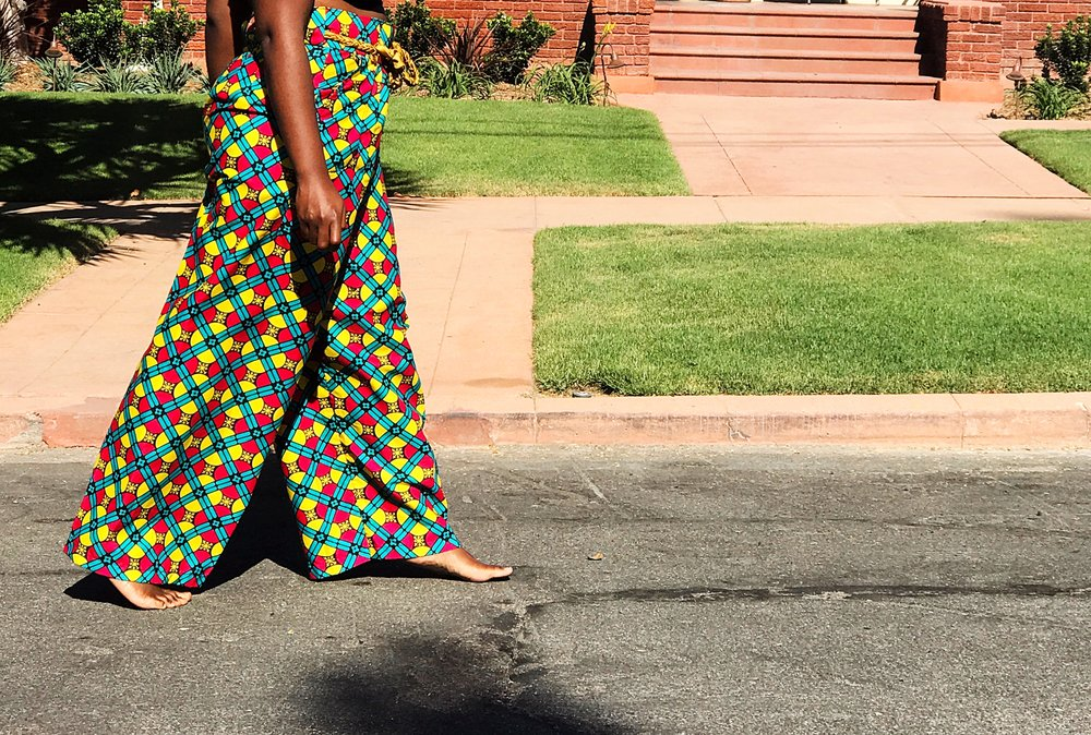 Black woman walking barefoot in street wearing wide leg ankara pants