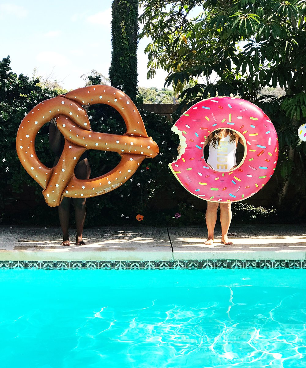 Two women standing next to pool holding pretzel and doughnut floaties