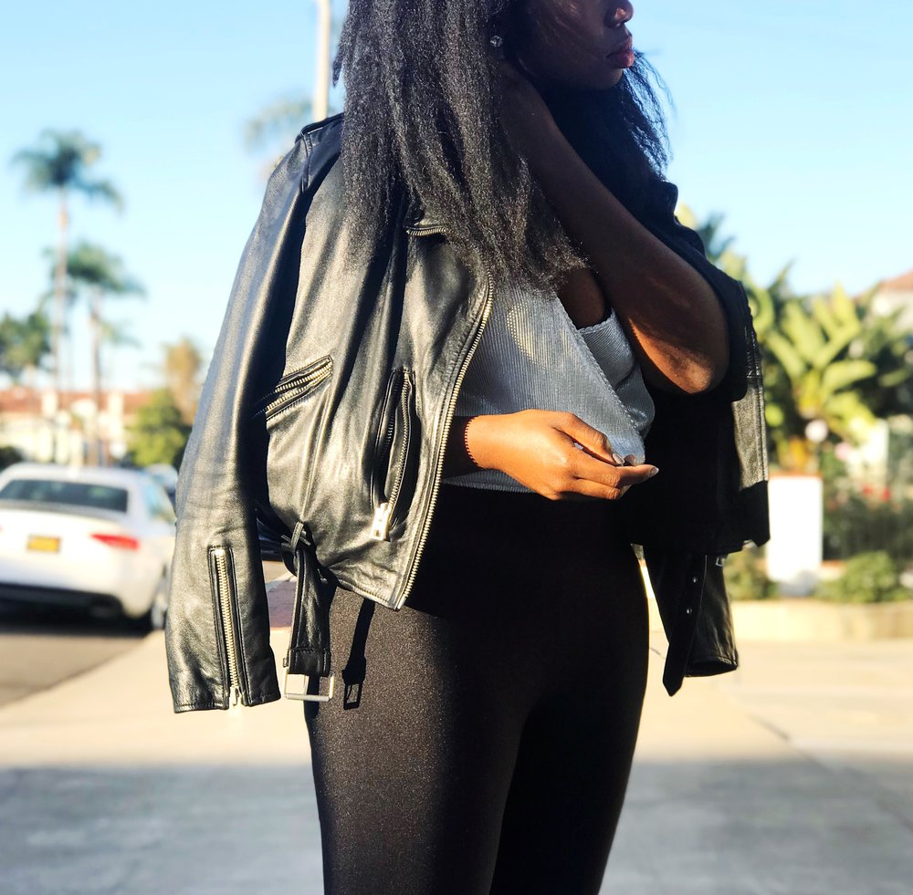 Femi in black leather jacket, black leggings, black strappy heels, silver tank.