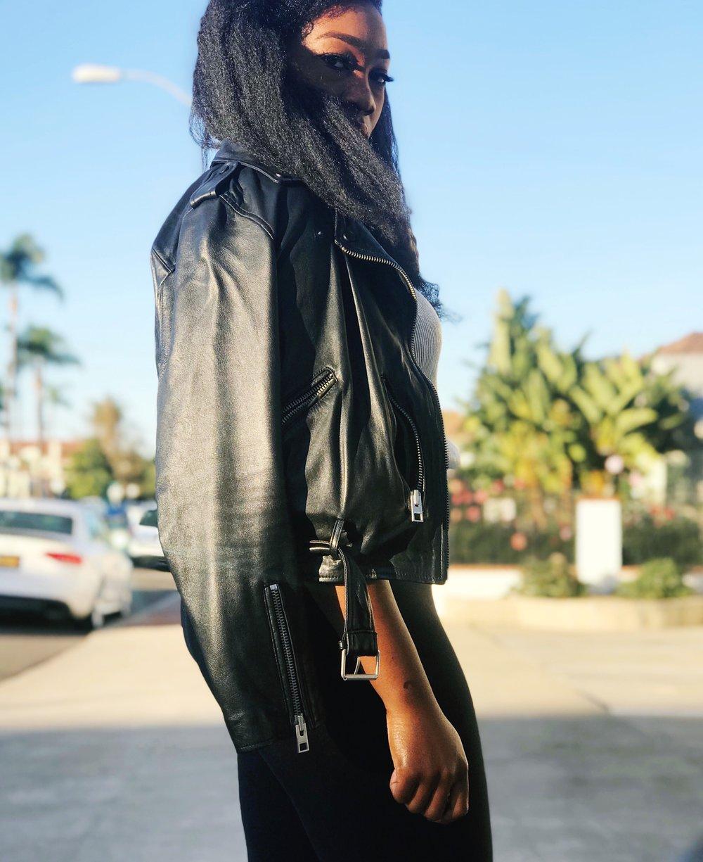 Femi in black leather jacket, black leggings, black strappy heels, silver tank.