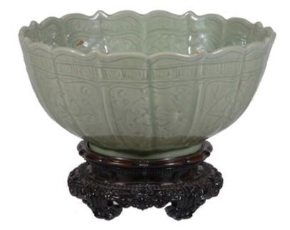 Lot 256, A 'Longquan' foliate-rimmed celadon bowl, Yuan/Ming Dynasty, incised with flowers and lappets of wave patterns, with carved wood stand Est. £6,000-8,000