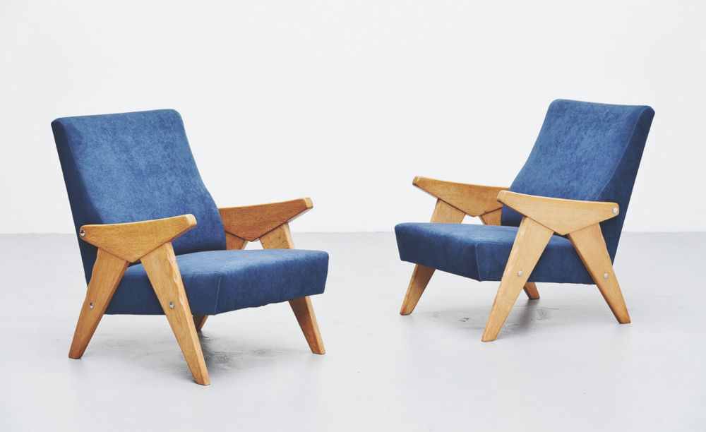 A pair of 1960s lounge chairs with a solid oak frame upholstered in blue velvet  www.massmoderndesign.com