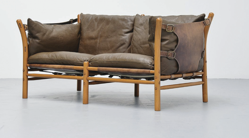 ILONA: Designed in the 60s, this two-seater sofa features a teak frame and brown leather, bound in by a heavy-duty leather backrest. The frame is typically held together by strong leather supports, without glue or screws