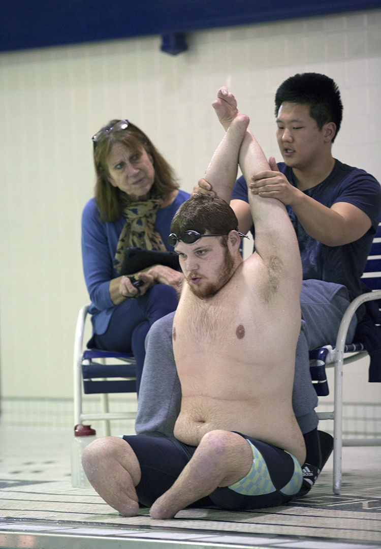 "Brame finishes an intense swimming training with five minutes of cool-down stretching of the waist and arm muscles. Coach Jane Brown and assistant coach Michele Hong discuss special training plans base on Brame's condition on February 17,2017. Brame is the first swimming athlete of the Penn State Ability Athletics program. ""Disability just a part of me, it doesn't defy me""."