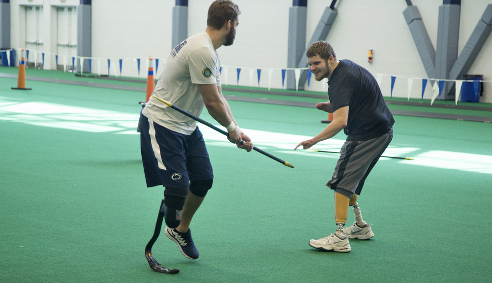 Brame playfully spars with Penn State Abilities Athlete Max Rohn after a morning workout at the Penn State Multi-Sport Facility. The two spend hundreds of hours training together each semester.