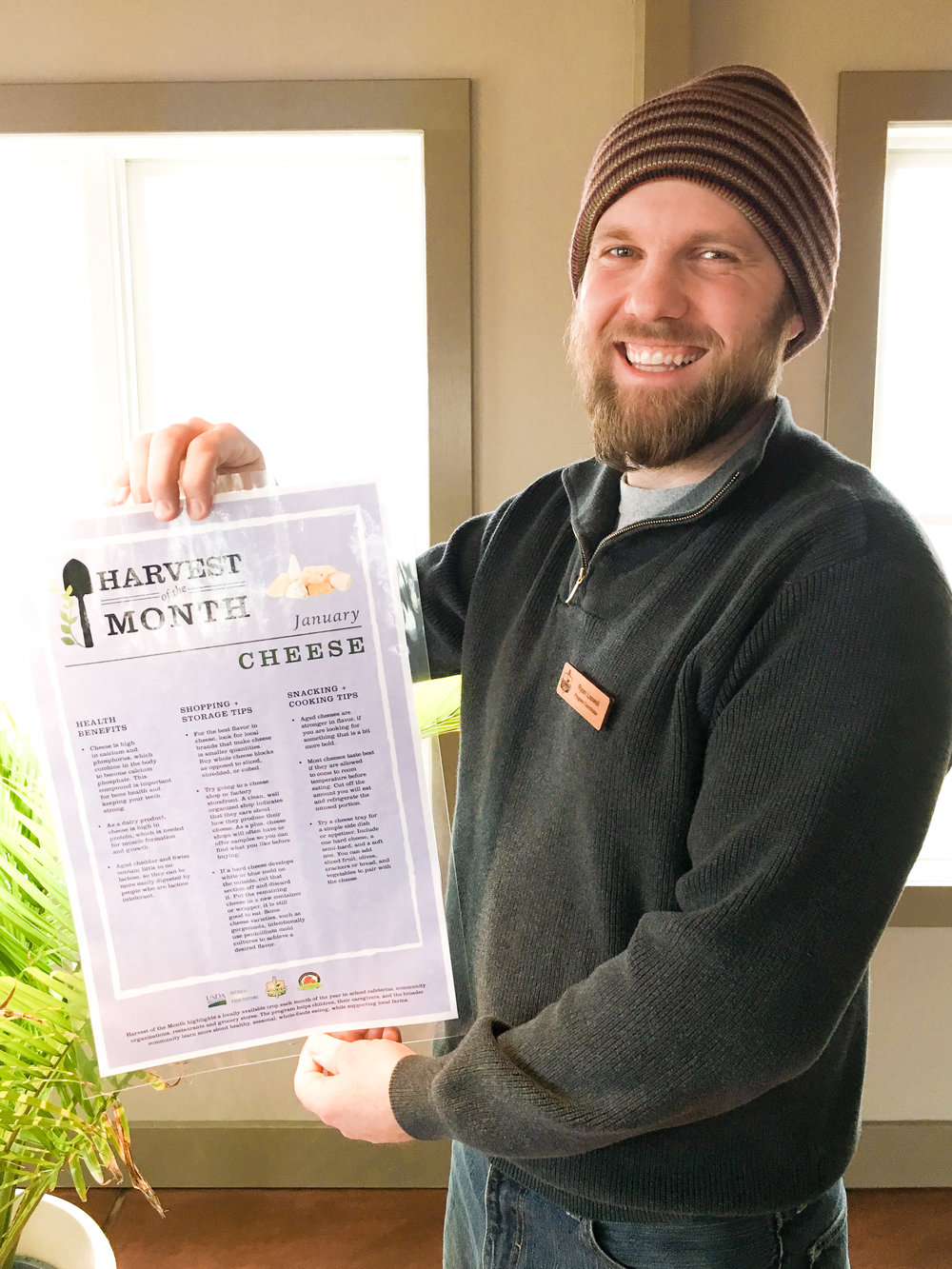 Program Manager, Ryan Laswell, with Harvest of the Month educational poster.