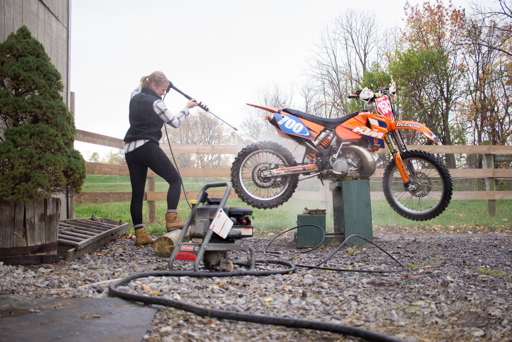 Mallory washes the mud from a previous race off her motorcycle. She likes to do all the work herself, from cleaning the bike to fixing it. 2016.