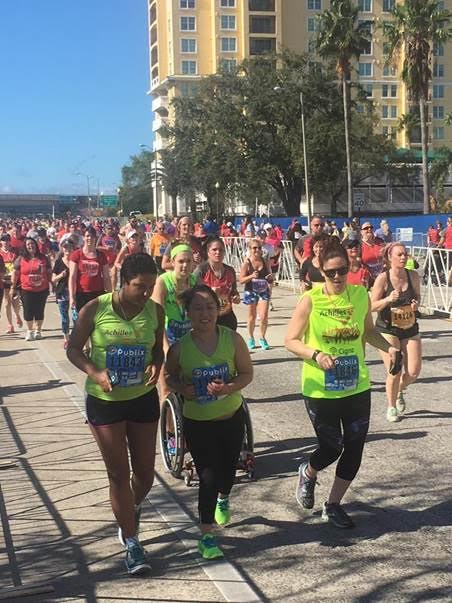 Athlete Jaime Hooker approaching the finish line of her first 5k with guides Holly Lynch & Joanna Craney