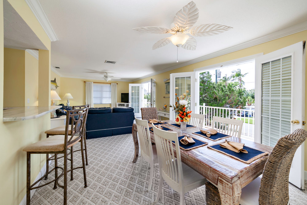 A great room features two French doors that open to a patio revealing a partial Gulf view.