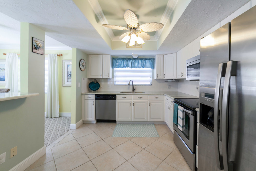 The renovated kitchen boasts stainless steel appliances and marble countertops.