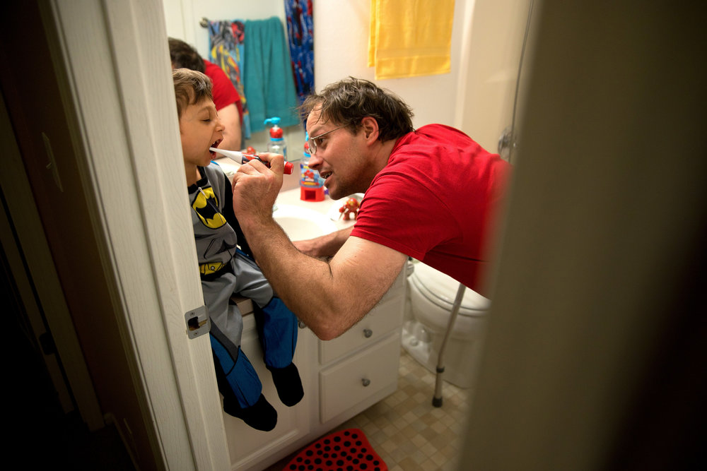Adam Timm brushes son Jahan Adam's teeth before bedtime in March.