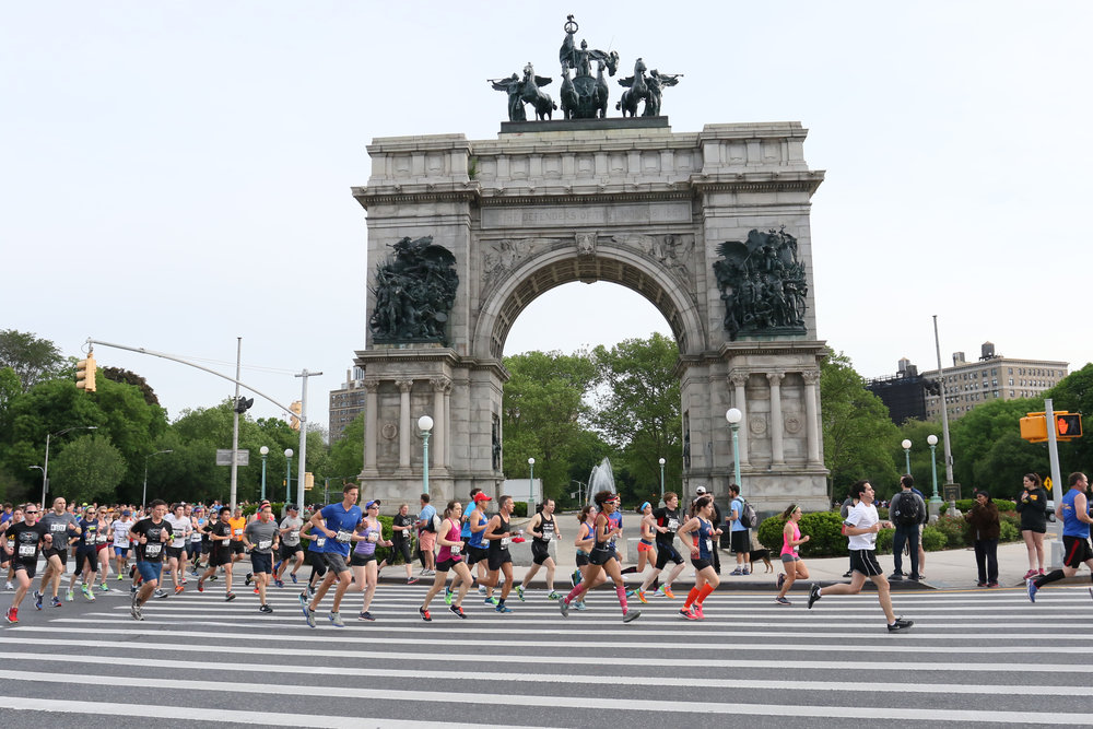 Runners round Grand Army Plaza on mile 2 of the Airbnb Brooklyn Half.