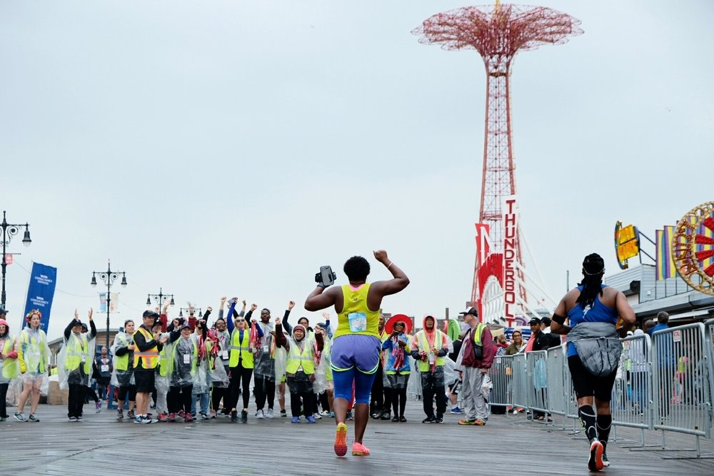 NYRR's dedicated volunteers welcome a Team for Kids runner to the finish on the Coney Island Boardwalk.