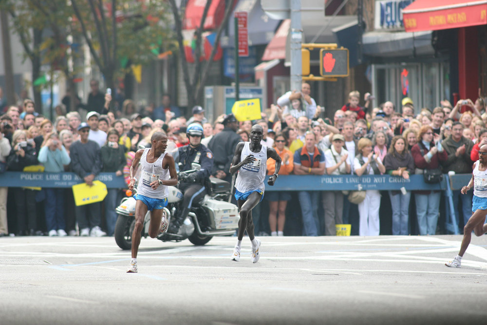 Ramaala speeds up turning onto First Avenue, while Keflezighi  (right of frame) stays in contact.