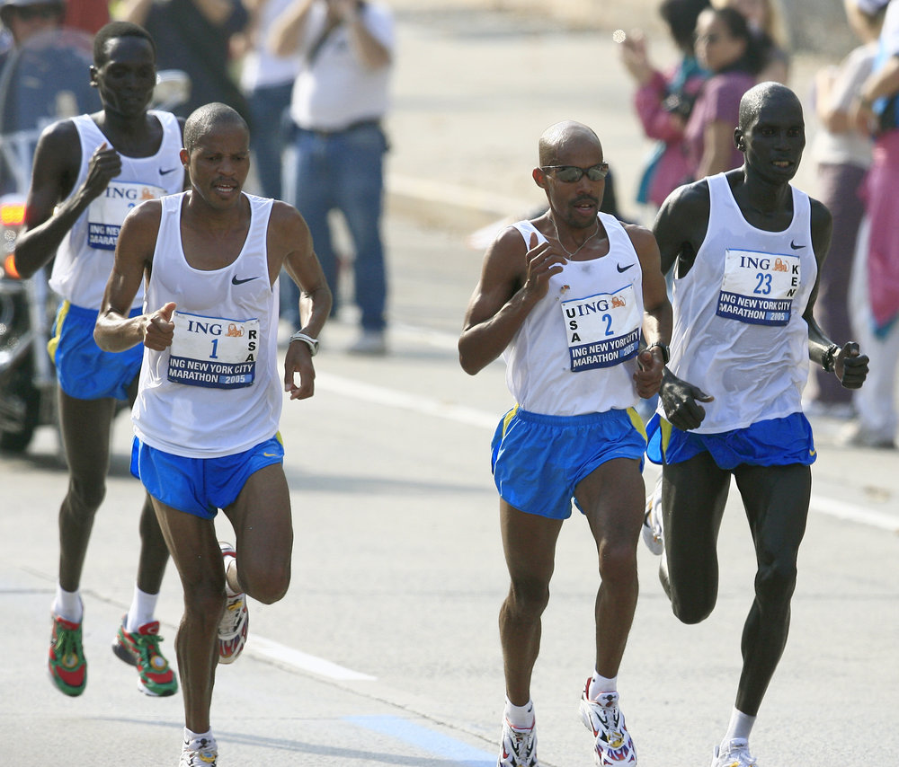 Ramaala, Keflezighi, and Cheruiyot at the front on First Avenue, with Tergat drafting behind the pack.