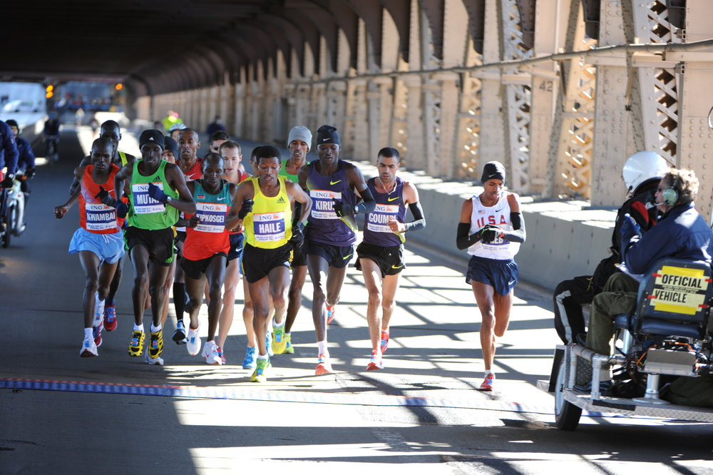 Keflezighi taking his mile 15 split on the Queensboro Bridge, with Gebrselassie to his right at the front of the pack.