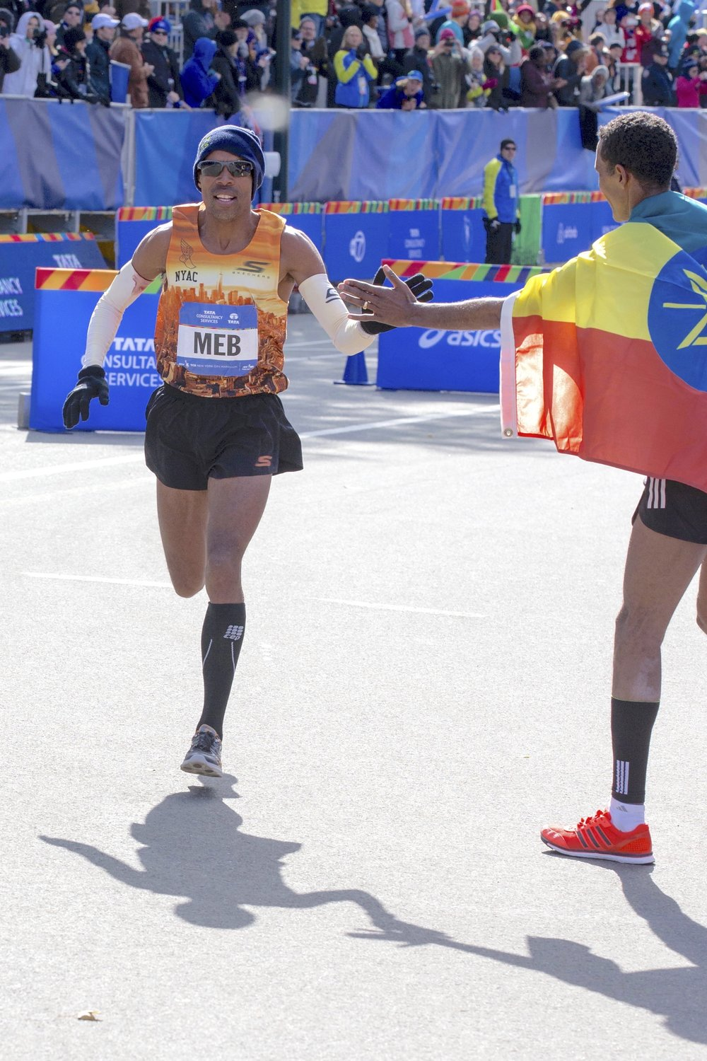 Gebre Gebremariam, the 2010 New York City Marathon champion, greets the 2009 champion on the homestretch