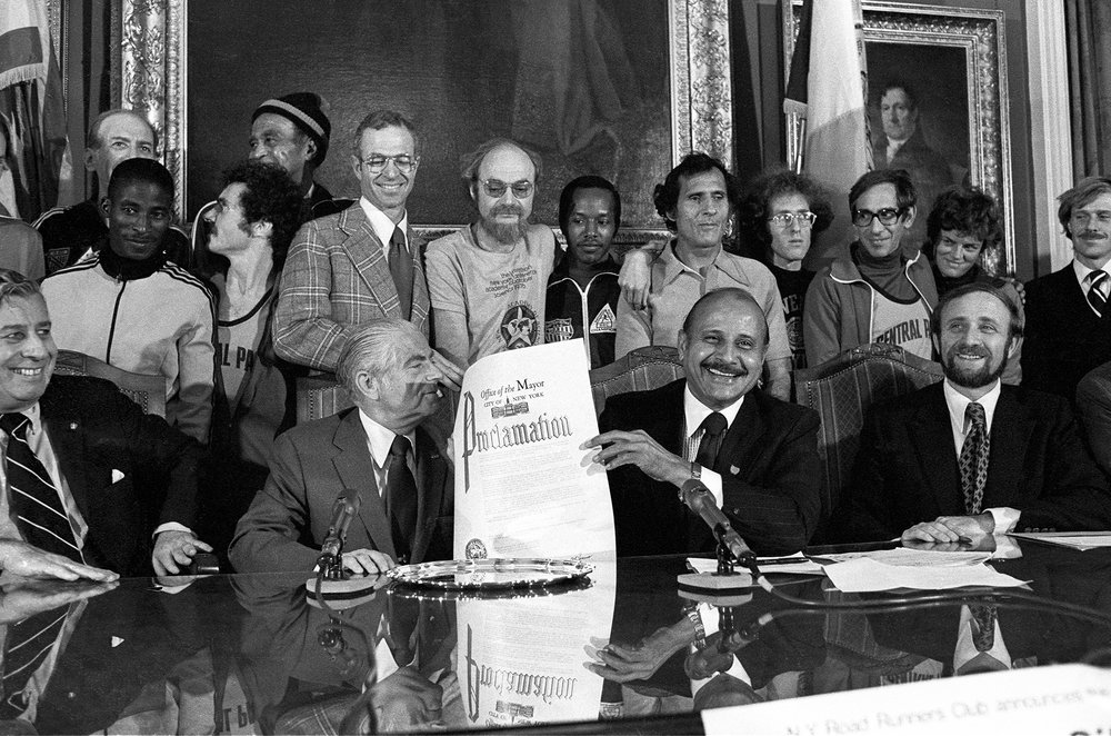 NYC Mayor Abe Beame, Manhattan Borough President Percy Sutton, and NYRR President Fred Lebow celebrate the city's proclamation for the inaugural five-borough New York City Marathon in October 1976.