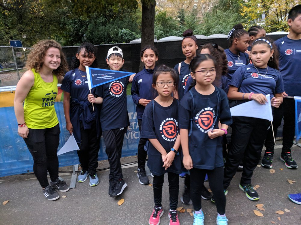 Coco paused for a photo with a group of Rising New York Road Runners during TCS New York City Marathon week in November 2017.