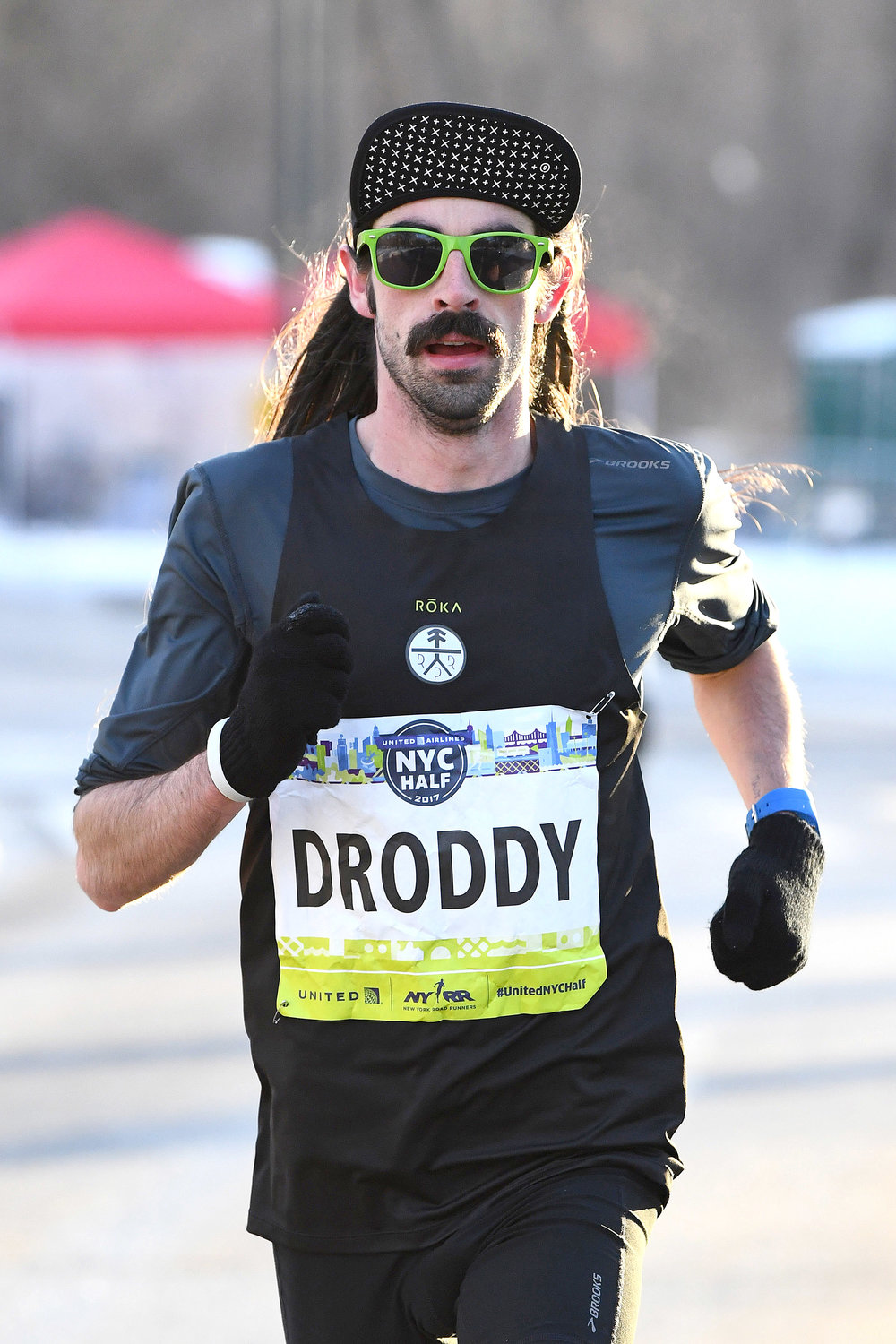 Noah Droddy—long hair, sunglasses, moustache, and all—racing to a new personal best at the 2017 United Airlines NYC Half.