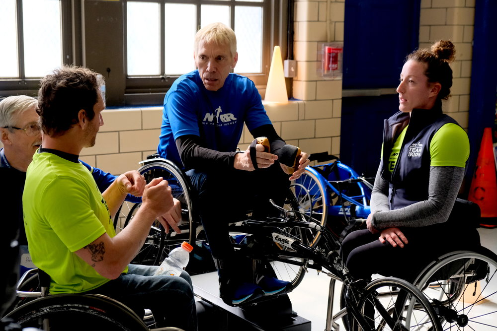 Peter Ciaccia, NYRR President, Events, and Race Director, TCS New York City Marathon, gets some pointers on wheelchair racing from Josh George and Tatyana McFadden.