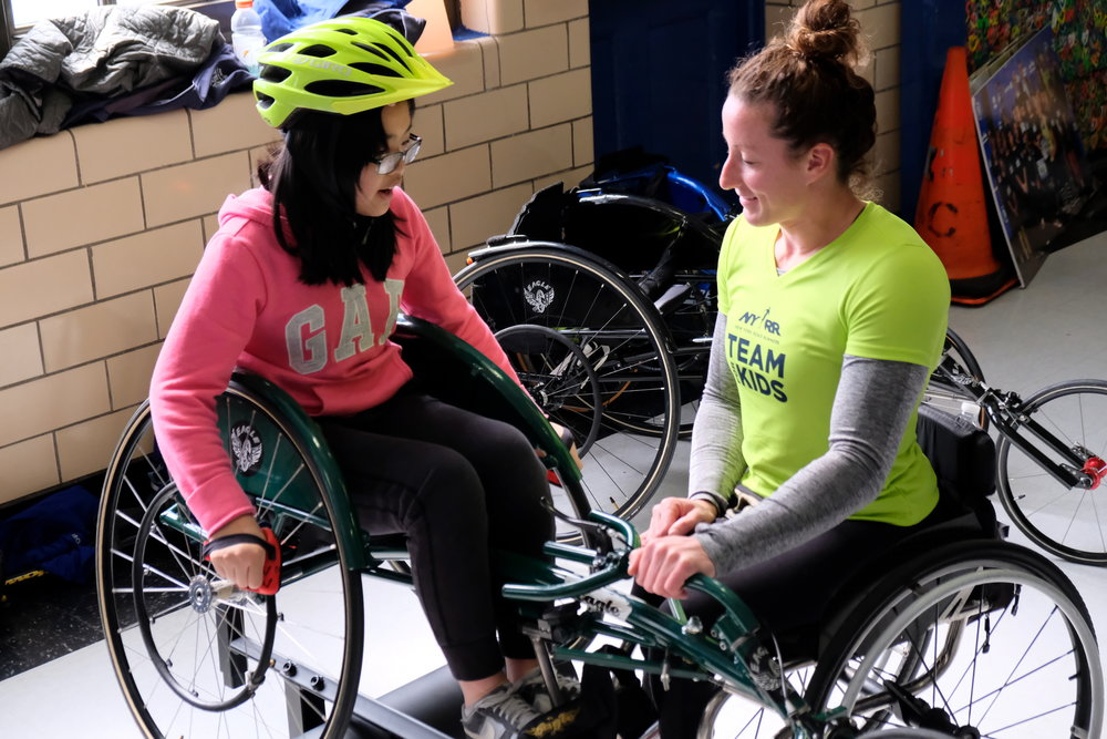 Tatyana McFadden encourages a student from P.S. 001 as they learn how to maneuver a racing wheelchair.