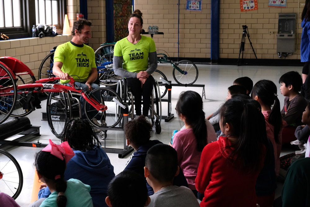 NYRR Team for Kids Ambassadors Josh George and Tatyana McFadden guide P.S. 001 students through the parts of a racing wheelchair before students took the chairs on a test ride.