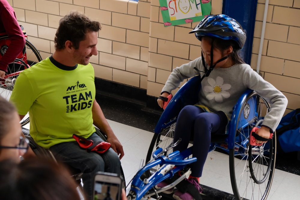 Josh George guides a P.S. 001 student on how to push a racing wheelchair.