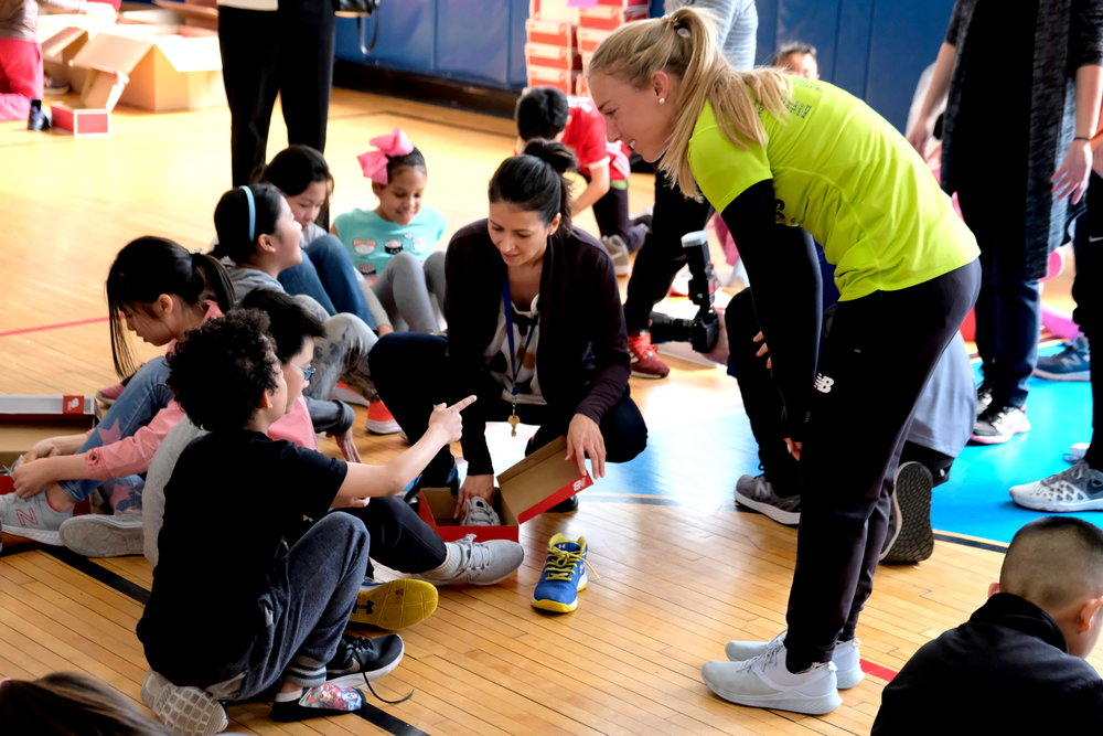 NYRR Team for Kids Ambassador Emily Sisson helps outfit P.S. 001 students with new pairs of New Balance running shoes.