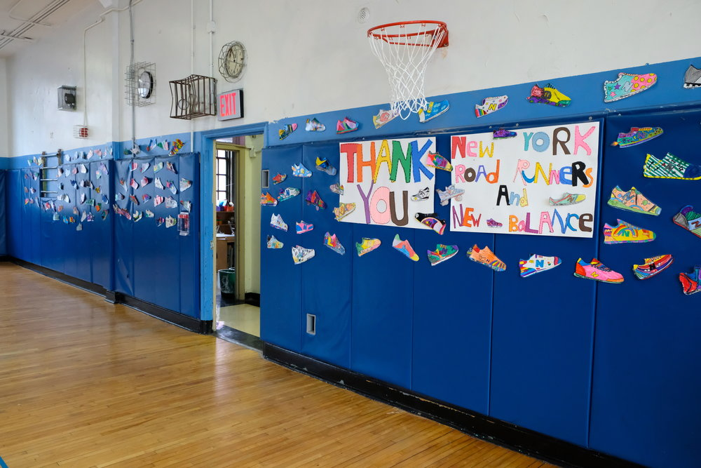 As dozens of pairs of shoes decorated the walls, in total approximately 325 students received new running shoes from NYRR and New Balance courtesy of the 1 for You 1 for Youth program.